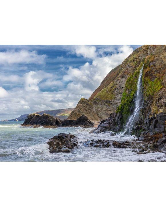 Lais Puzzle - Ein Wasserfall an der walisischen Küste in dem kleinen Fischerdorf Tresaith. Das Meer ist wild, ebenso wie der weiß-blaue Wolkenhimmel. Im Hintergrund die hohen Klippen - 500 & 1.000 Teile